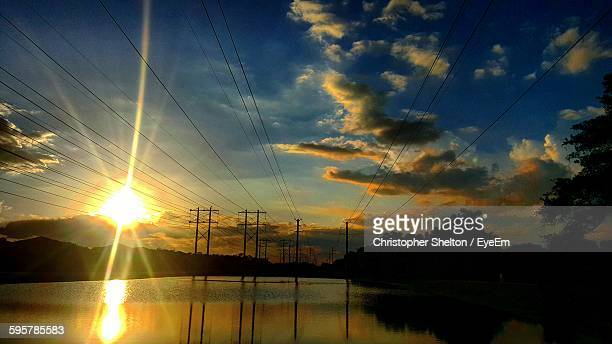 River With Silhouette Electricity Pylons Against Cloudy Sky During Sunset