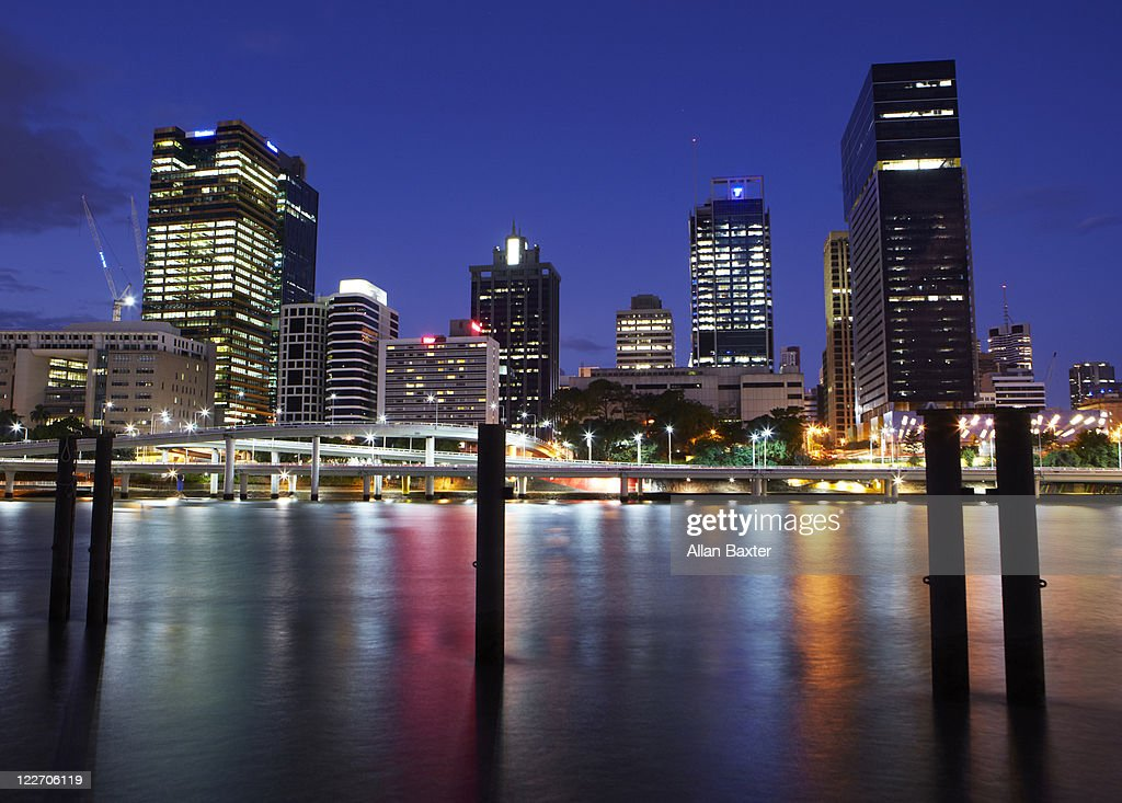 River with skyscrapers illuminated at night : Stock Photo