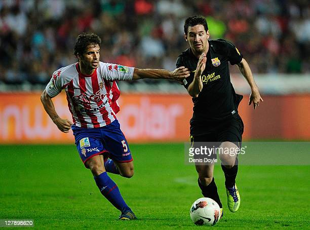 Rivera of Real Sporting de Gijon grabs the arm Leo Messi of FC Barcelona during the La Liga match between Real Sporting de Gijon and FC Barcelona at...