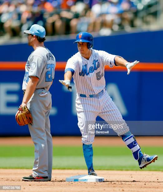 J Rivera of the New York Mets celebrates his double at second base as Daniel Murphy of the Washington Nationals looks away in an MLB baseball game on...