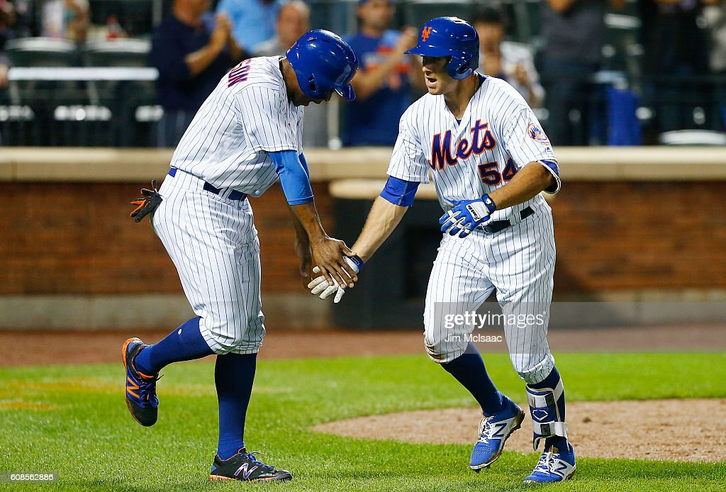 T.J. Rivera #54 of the New York Mets celebrates his fourth-inning, two-run home run against the Atlanta Braves with teammate Curtis Granderson #3 at Citi Field on September 19, 2016 in the Flushing neighborhood of the Queens borough of New York City.