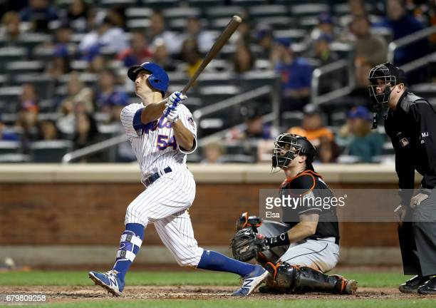 J Rivera of the New York Mets hits a single in the fifth inning as JT Realmuto of the Miami Marlins defends on May 6 2017 at Citi Field in the...