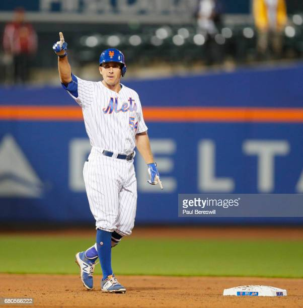 TJ Rivera of the New York Mets holds his finger in the air while looking at his teammates in the dugout after hitting a 2 rbi double in the 7th...