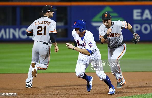 J Rivera of the New York Mets is caught in a rundown by Joe Panik and Brandon Crawford of the San Francisco Giants in the fifth inning during their...