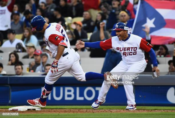 J Rivera of the Puerto Rico runs by his firstbase coach after hitting a home run to give them a 32 lead in the second inning against team Netherlands...