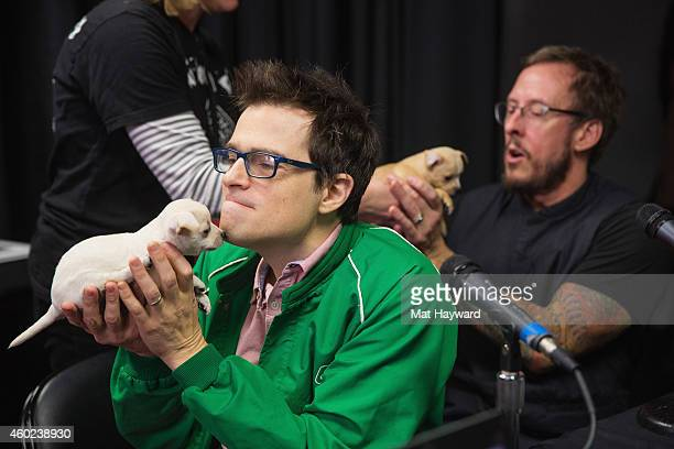 Rivers Cuomo and Scott Shriner of Weezer hold puppies brought by Motley Zoo Animal rescue backstage during Deck the Hall Ball hosted by 1077 The End...