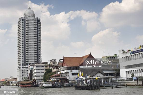 A riverscape along the Chao Phraya River includes a large condominium and some older apartment blocks
