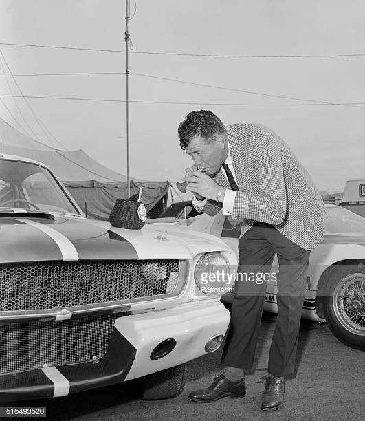 Cobra sports car builder Carroll Shelby whose Ford powered cars have been a constant contender in International racing plays a toy flute to charm a...