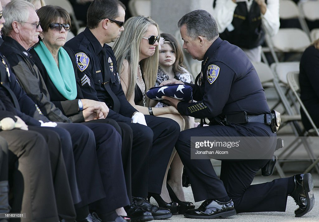 Riverside Police Chief Sergio Diaz presents the flag to Regina Crain, wife of officer Officer Michael Crain, during his committal ceremony at Riverside National Cemetery on February 13, 2013 in Riverside, California. Officer Crain was allegedly killed by ex LAPD officer Chris Dorner on February 7, 2013.