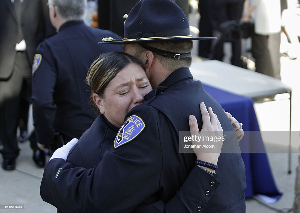 Riverside police officers embrace following the committal ceremony of officer Michael Crain at Riverside National Cemetery on February 13, 2013 in Riverside, California. Officer Crain was allegedly killed by ex LAPD officer Chris Dorner on February 7, 2013.