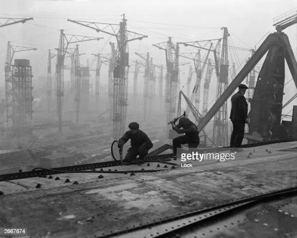 Riveters at work on the top deck of the new Cunard White Star liner Queen Mary under construction at the John Brown Co shipyard Clydebank