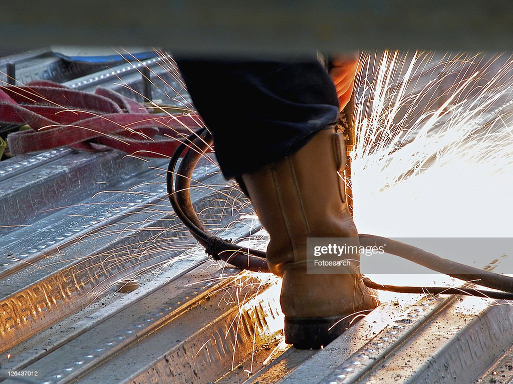 Riveter's boot with sparks flying from hot rivet driven into floor plate