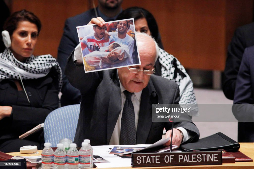 Riyad H Mansour Palestine's Ambassador to the United Nations holds up a picture from the Israeli operation in Gaza during a Security Council meeting...