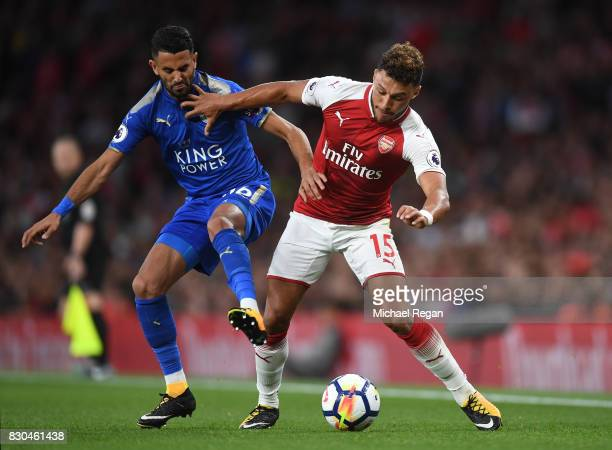 Riyad Mahrez of Leicester City and Alex OxladeChamberlain of Arsenal compete fr the ball during the Premier League match between Arsenal and...