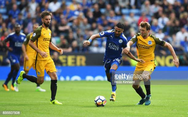Riyad Mahrez of Leicester City and Dale Stephens of Brighton and Hove Albion battle for possession during the Premier League match between Leicester...