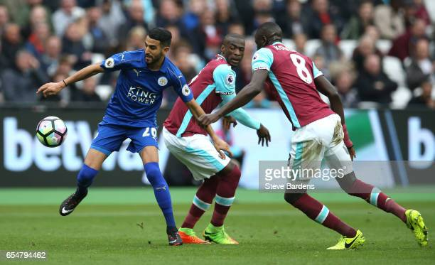 Riyad Mahrez of Leicester City attempts to escape a challenge from Cheikhou Kouyate of West Ham United during the Premier League match between West...