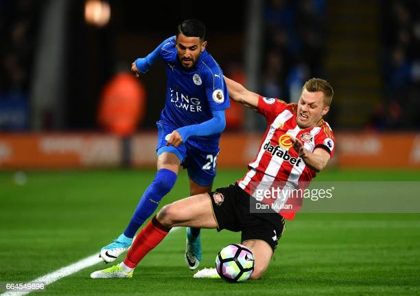 Riyad Mahrez of Leicester City attempts to escape a challenge from Sebastian Larsson of Sunderland during the Premier League match between Leicester...