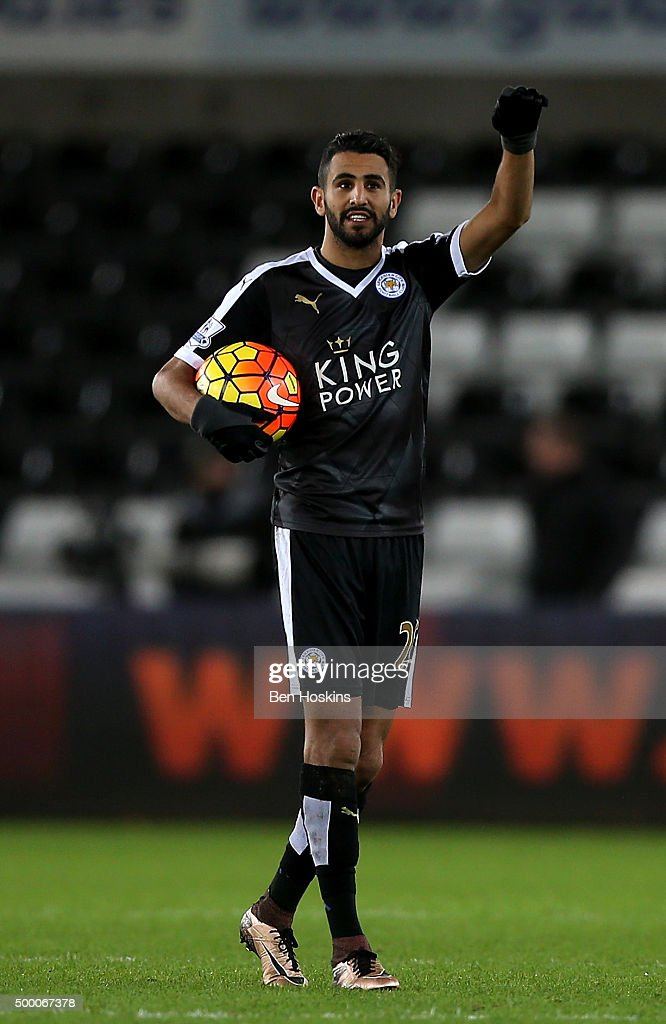 Riyad Mahrez of Leicester City celebrates his hat trick with the match ball after the Barclays Premier League match between Swansea City and Leicester City at Liberty Stadium on December 5, 2015 in Swansea, Wales.