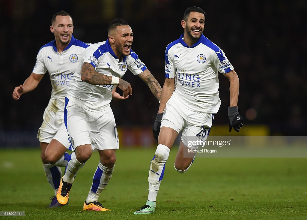 Riyad Mahrez (R) of Leicester City celebrates scoring his team's first goal with his team mates Danny Drinkwater (L) and Danny Simpson (C) during the Barclays Premier League match between Watford and Leicester City at Vicarage Road on March 5, 2016 in Watford, England.