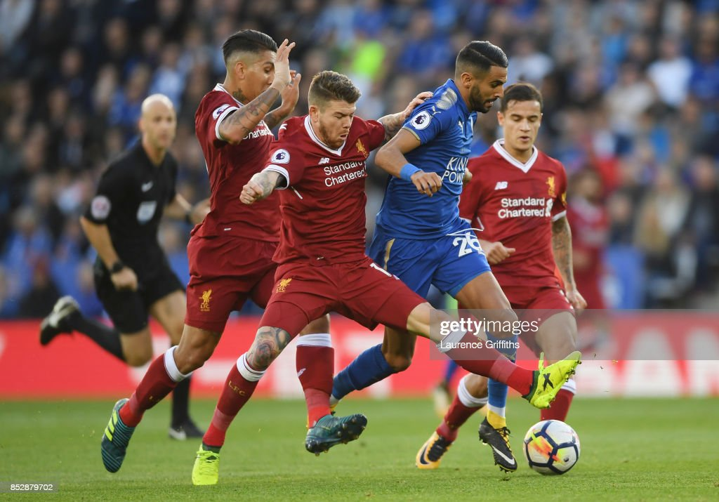 Riyad Mahrez of Leicester City comes under pressure from Alberto Moreno, Roberto Fimino and Philippe Coutinho of Liverpool during the Premier League match between Leicester City and Liverpool at The King Power Stadium on September 23, 2017 in Leicester, England.