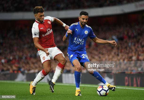 Riyad Mahrez of Leicester City is challenged by Alex OxladeChamberlain of Arsenal during the Premier League match between Arsenal and Leicester City...