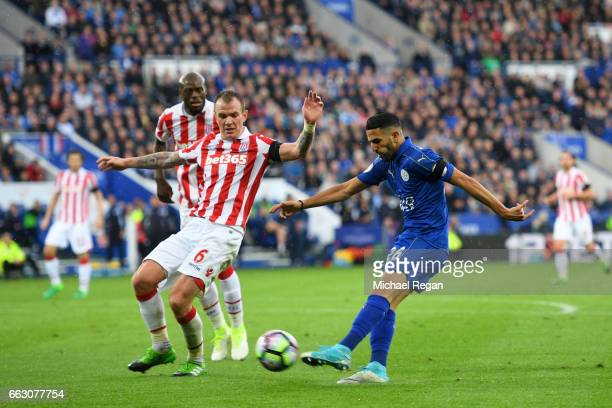 Riyad Mahrez of Leicester City shoots as Glenn Whelan of Stoke City attempts to block during the Premier League match between Leicester City and...
