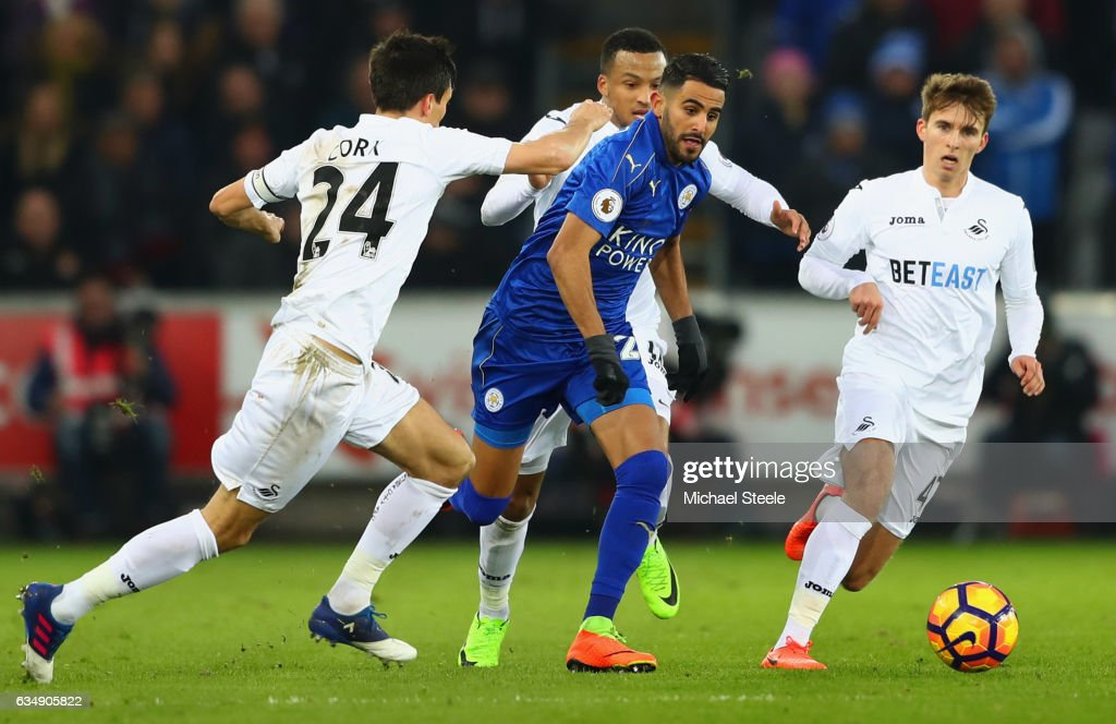 Riyad Mahrez of Leicester City takes on Jack Cork (L), Martin Olsson and Tom Carroll of Swansea City (R) during the Premier League match between Swansea City and Leicester City at Liberty Stadium on February 12, 2017 in Swansea, Wales.