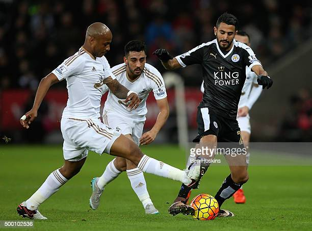 Riyad Mahrez of Swansea skips past the tackle of Andrew Ayew of Swansea during the Barclays Premier League match between Swansea City and Leicester...