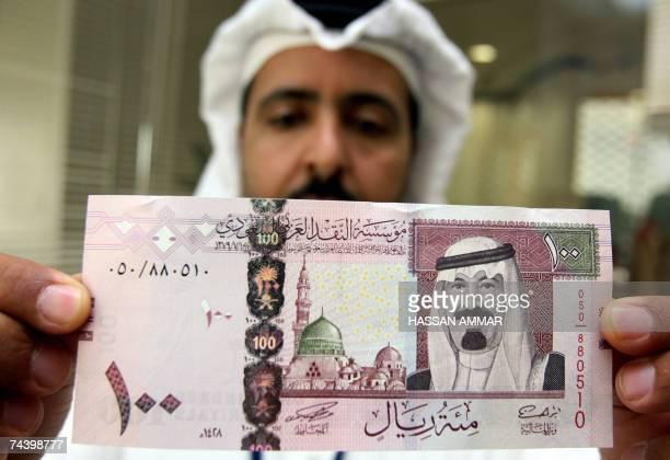 A Saudi banker displays the new one hundred riyal banknote bearing the portrait of Saudi King Abdullah bin Abdul Aziz alSaud at a bank in Riyadh 05...