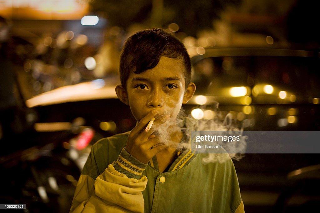 Rizki, age 15, smokes in the street on January 25, 2011 in Yogyakarta, Indonesia. It is estimated that over 25 percent of children in Indonesia over the age of three have tried smoking, with over three percent of them smoking regularly. The lack of government regulation around advertising is blamed for the problem, with campaigns seen heavily at sporting events, music concerts. The Indonesian government previously passed a health bill in 2009 to address the issues, but it has not yet been implemented.
