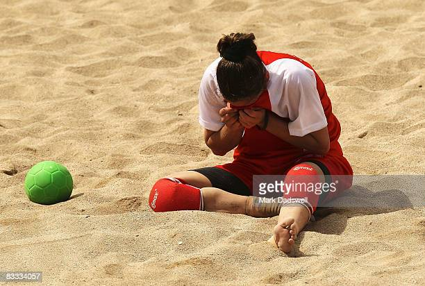 Roa'a Naser of Jordan rubs sand from her eyes after falling hard in the Womens Beach Handball against Hong Kong China on day one of the 2008 Asian...