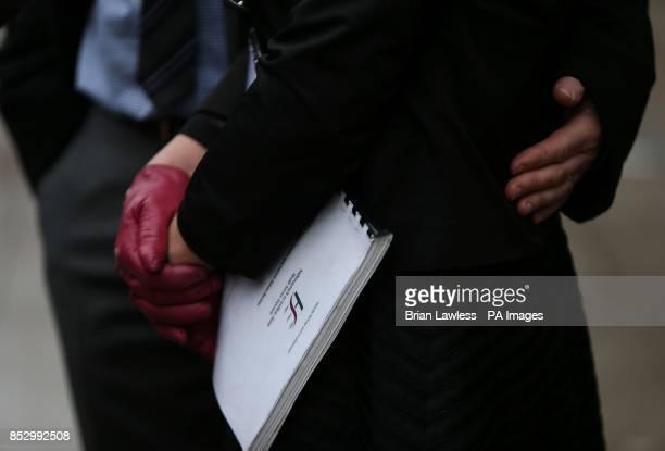 Roacuteisiacuten Molloy holds a Health Service Executive document as her husband Mark Molloy places a hand on her back outside Leinster House Dublin...