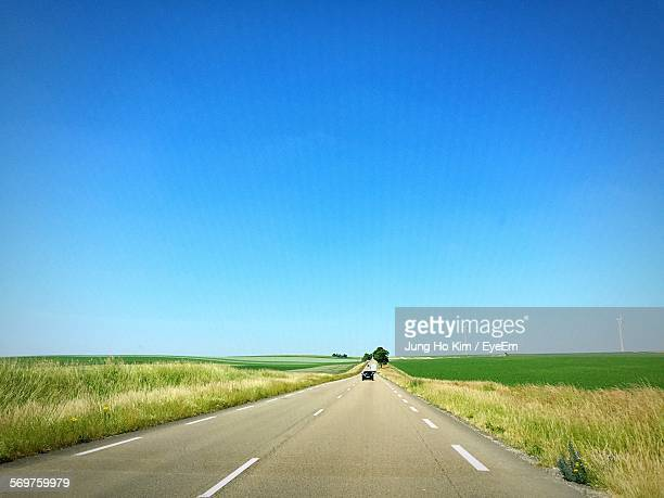 Road Amidst Field Against Clear Blue Sky