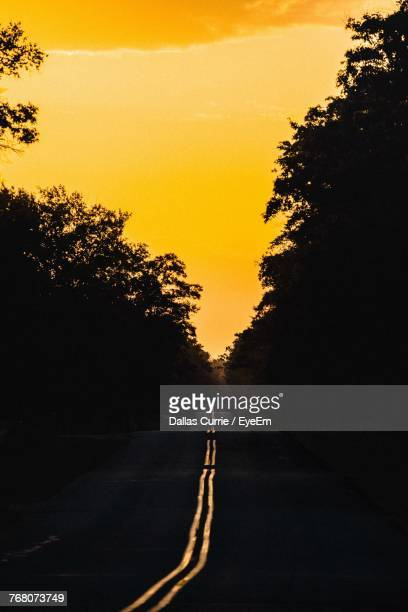 Road Amidst Silhouette Trees Against Sky At Sunset