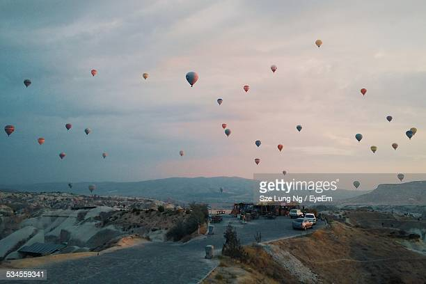 Road And Hot Air Balloons Against Cloudy Sky At Dusk