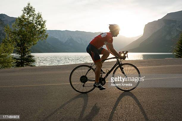 Road biker follows mountain road, sunrise