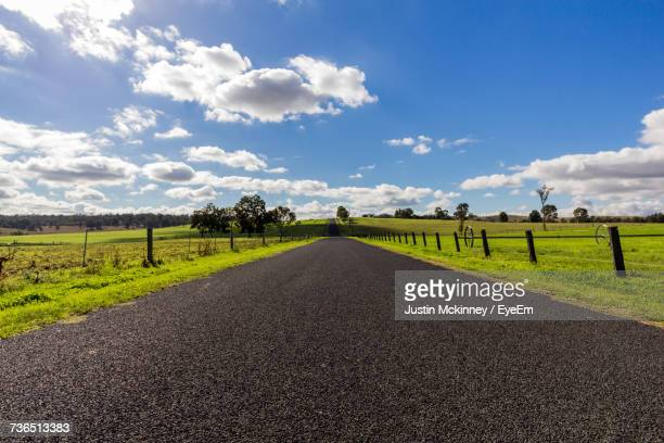 Road By Agricultural Field Against Sky