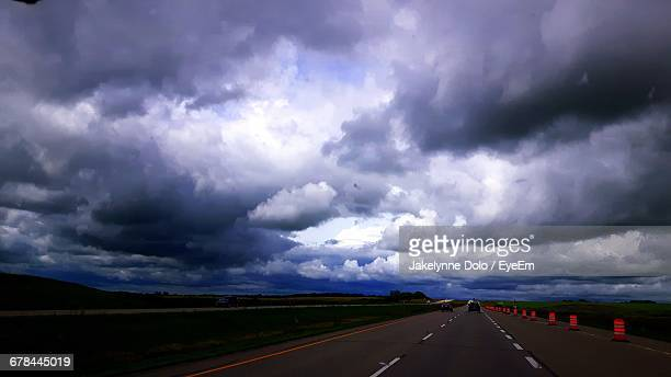 Road By Field Against Cloudy Sky