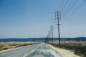 Road By Telephone Poles On Field Against Clear Blue Sky