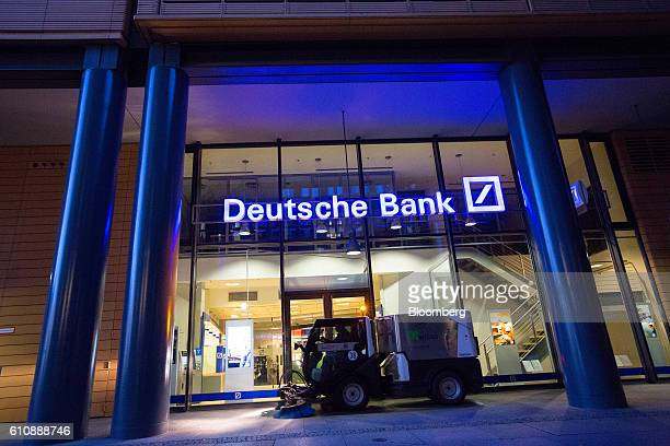 A road cleaning machine drives past the exterior of a Deutsche Bank AG bank branch in Berlin Germany on Wednesday Sept 28 2016 Deutsche Bank AG rose...