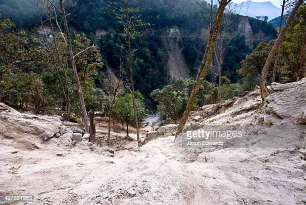 Road construction causes a landslide of soil and rocks destroys on a Himalayan mountainside.