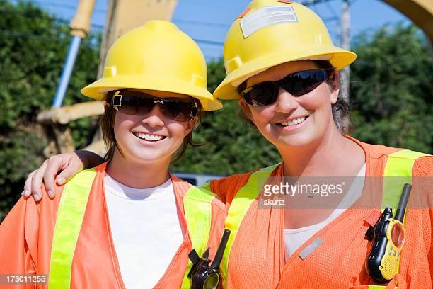 Road Construction women working safety gear bright orange helmet