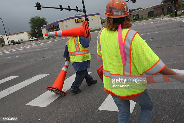 Road construction workers collect cones at the end of the day on a project funded by federal stimulus funds on May 21 2009 in Littleton Colorado The...
