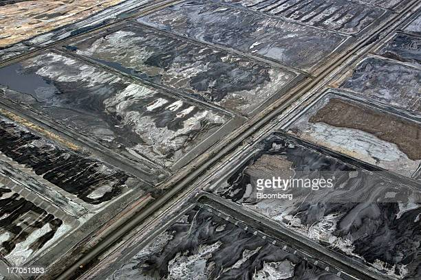 A road cuts through the oil sands at a Suncor Energy Inc oil sands mining operation near Fort McMurray Alberta Canada on Tuesday Aug 13 2013 Canadian...
