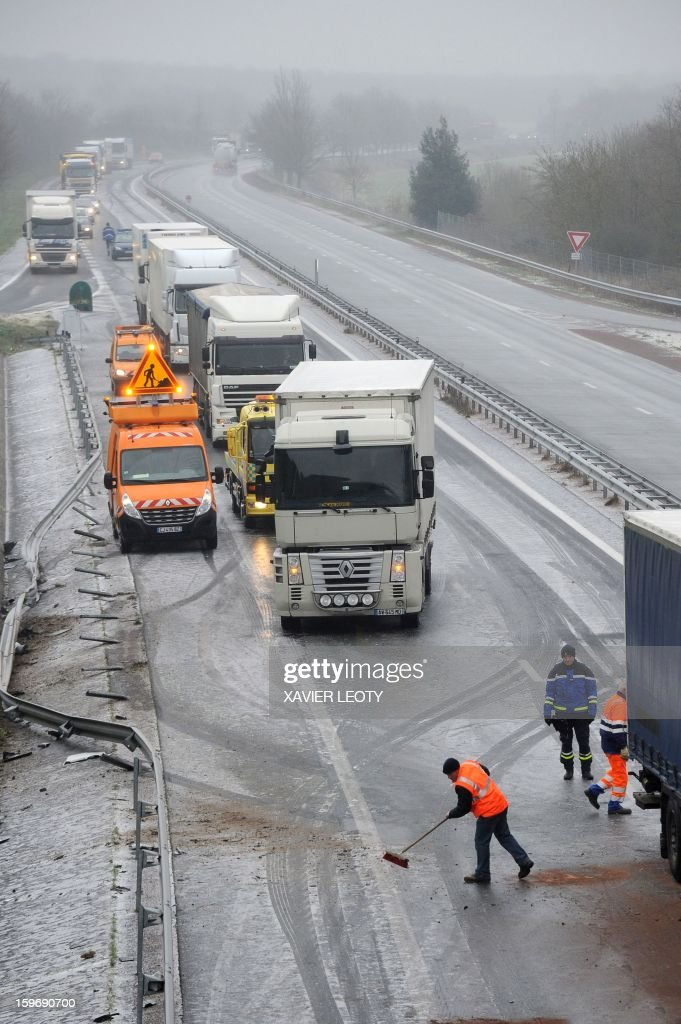 Road employees are at work on an ice-covered road after a crash due to freezing rain, on January 18, 2013 on the RN11 near Ferrieres. Thirty-seven French departments are under medium range (orange) alert due to the inclement weather.