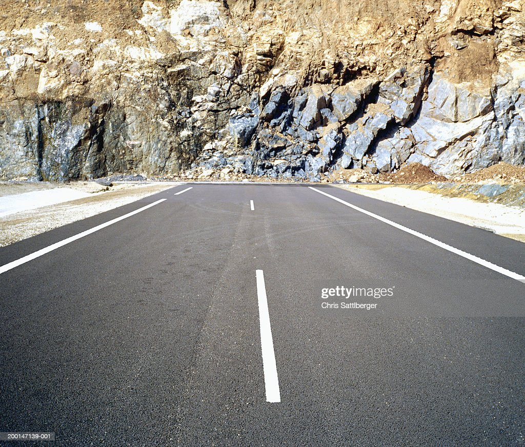 Road ending at rugged rockface : Stock Photo