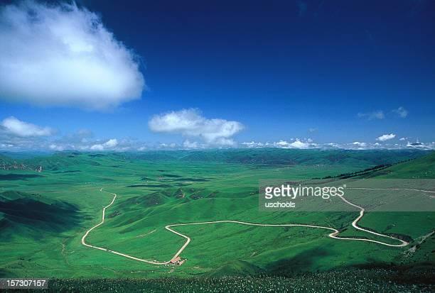 Estrada que se prolongam para dentro em prado verde horizonte distante