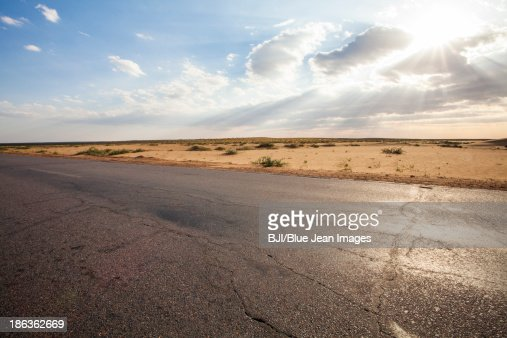 Road going through desert on a clear day in Inner Mongolia province, China