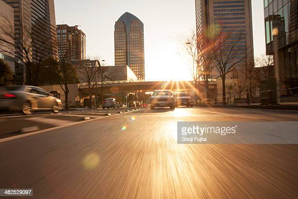 Road in city with car and sunlight