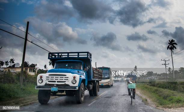 Road in Cuba with a cyclist and a old truck in a rainy day leaving Pinar del Rio City.